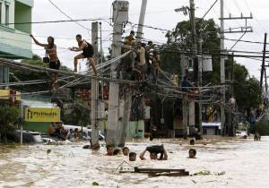 Residents clamber on electric wires to stay out of floodwaters while others wade neck-deep in Cainta Rizal, east of Manila.