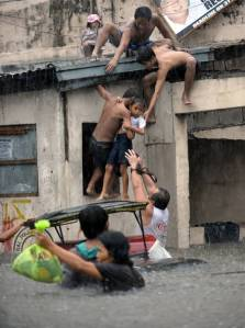 A boy is lifted onto the roof of a building to escape the flooding in the Quezon City suburban of Manila.